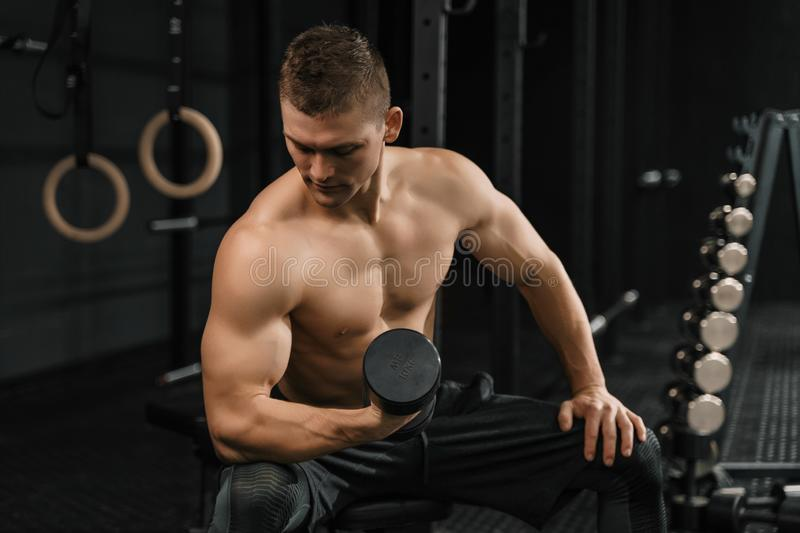 Handsome power athletic man bodybuilder doing exercises. With dumbbell in a gym. Crossfit training royalty free stock photography