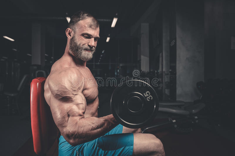 Handsome power athletic man on diet training pumping up muscles stock photography