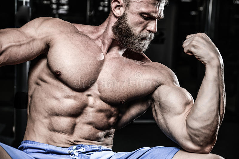 Handsome power athletic man on diet training pumping up muscles royalty free stock photo