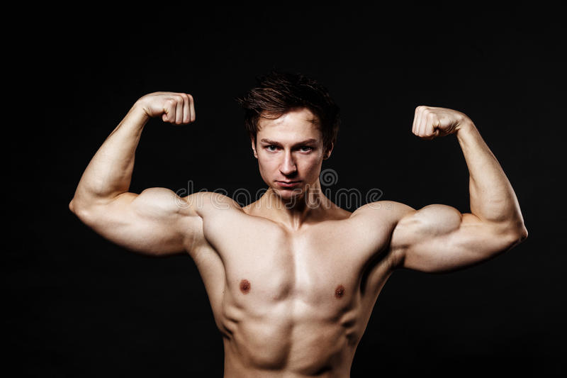 Handsome power athletic man with dumbbell confidently looking forward. Strong bodybuilder with six pack, perfect stock images