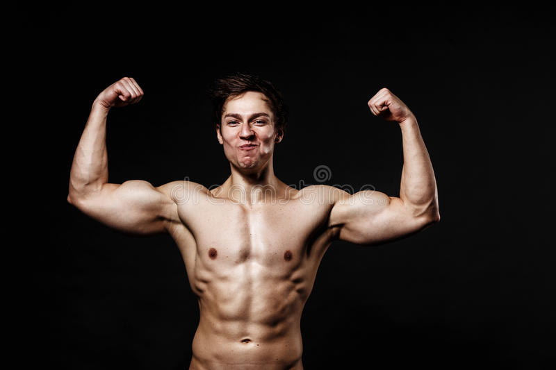 Handsome power athletic man with dumbbell confidently looking forward. Strong bodybuilder with six pack, perfect royalty free stock photo