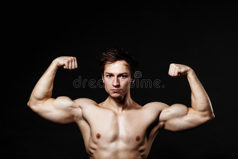 Handsome power athletic man with dumbbell confidently looking forward. Strong bodybuilder with six pack, perfect stock photo