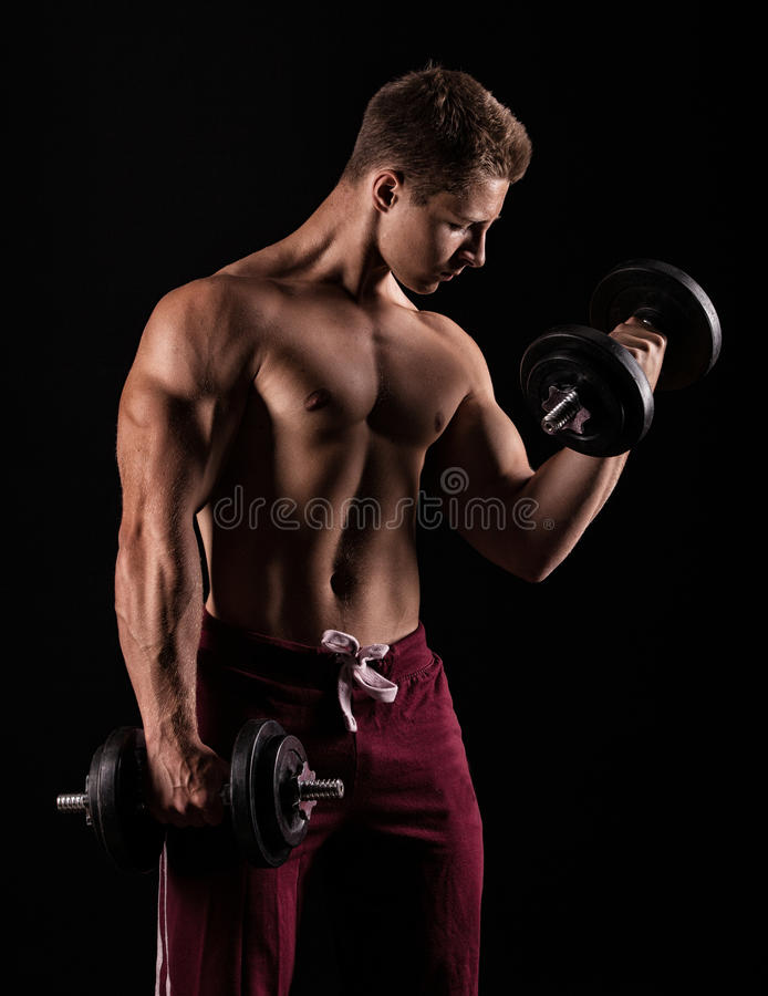 Handsome power athletic man with dumbbell confidently looking forward. royalty free stock images