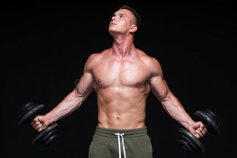 Handsome power athletic man with dumbbell confidently looking forward. Strong bodybuilder with six pack, perfect abs. Shoulders, biceps, triceps and chest royalty free stock images