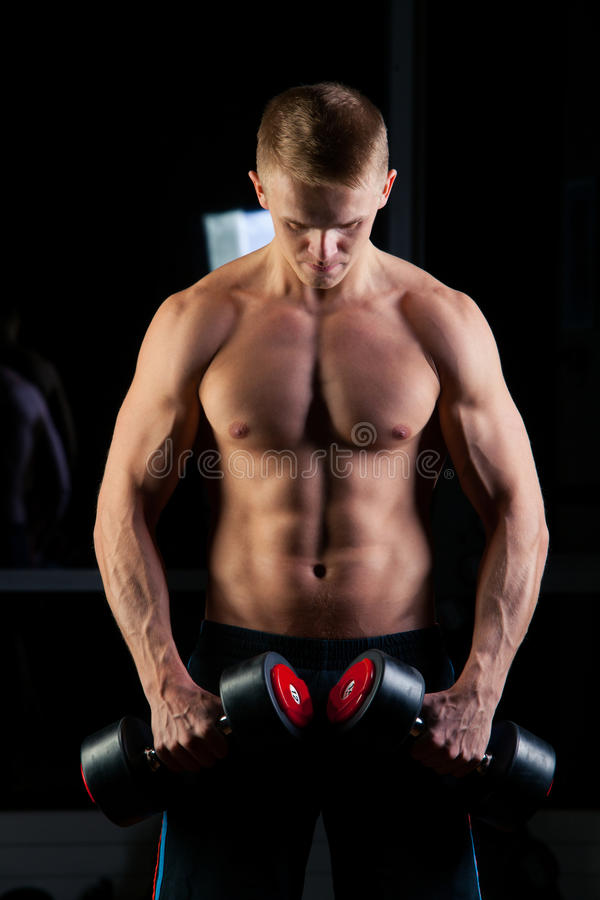 Handsome power athletic man with dumbbell confidently looking forward. Strong bodybuilder six pack, perfect abs stock photo