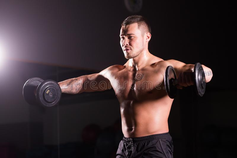 Handsome power athletic man with dumbbell. Strong bodybuilder with six pack, perfect abs, shoulders, biceps, triceps and royalty free stock photos