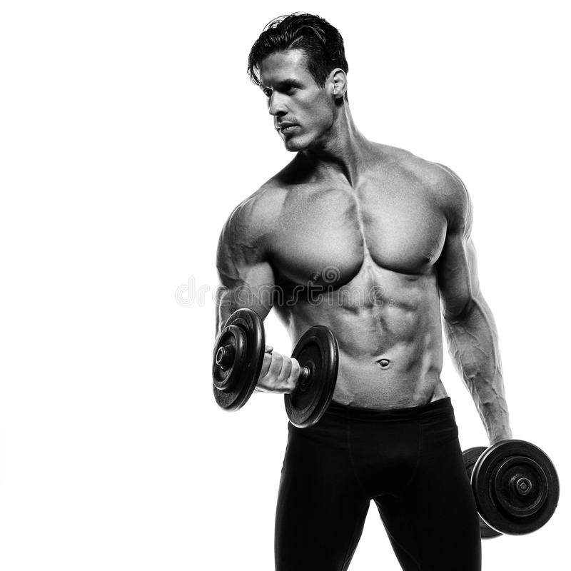 Handsome power athletic man in training pumping up muscles with stock photography
