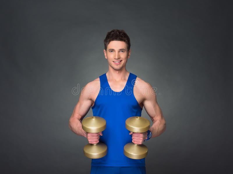 Handsome power athletic man in training pumping up muscles with dumbbells in a gym. Blue t-shirt stock photography