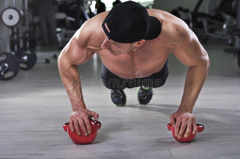 Handsome powerful athletic man performing push ups with kettle bell. Strong bodybuilder with perfect shoulders, biceps and triceps stock image