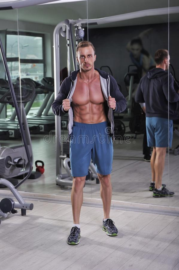 Handsome powerful athletic man posing at the gym. Strong bodybuilder with six pack, perfect abs and chest royalty free stock image