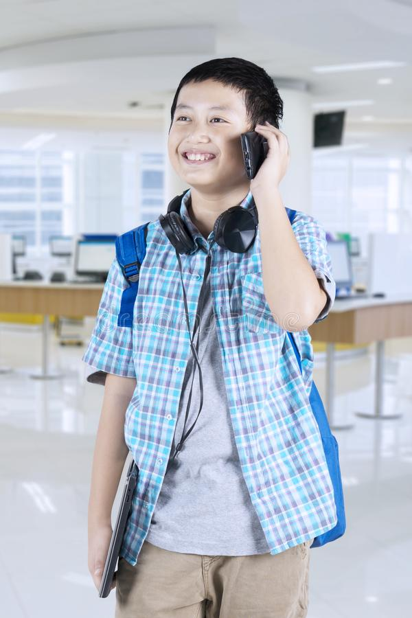 Handsome preteen student talking on the phone stock photography