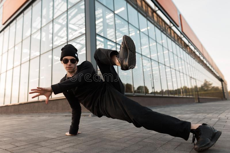 Handsome pretty young hipster man in stylish black clothes in a fashionable knitted hat in leather sneakers poses. Near a modern glass building. Urban guy royalty free stock photo