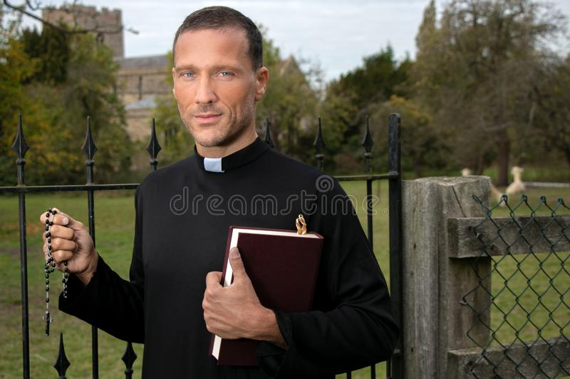 Good looking priest standing next to iron gate holding bible with field, alpacas and church in background. Handsome priest standing next to iron gate holding stock images