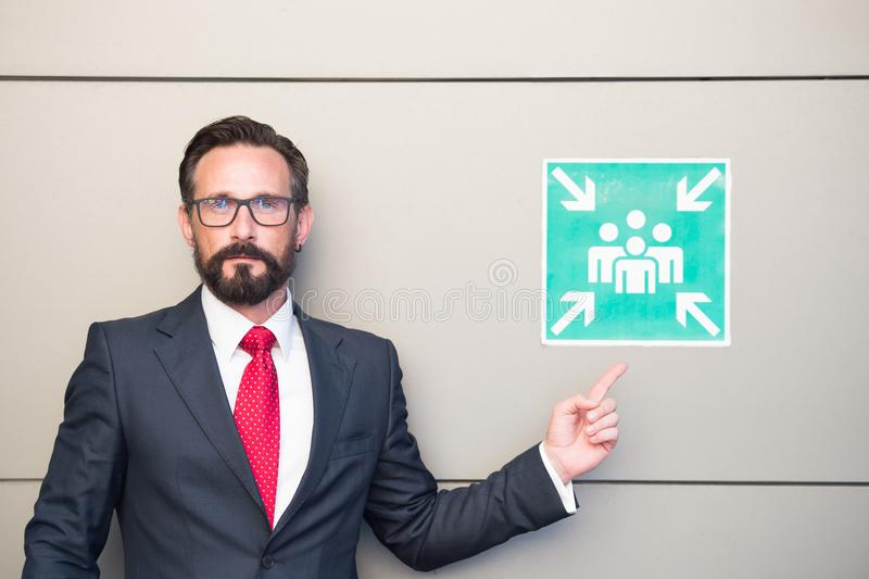 Handsome professional leader pointing to meeting point sign. Man in suit and red tie warning about meeting point. stock image