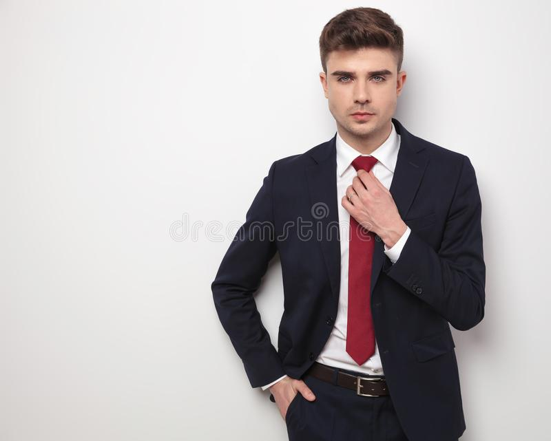 Handsome relaxed businessman fixing his red tie while standing stock images