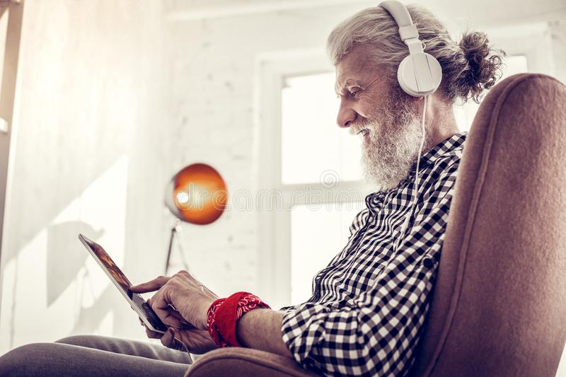 Handsome retired man testing modern gadget at home. Being pleased. Kind bearded male expressing positivity while spending weekend with pleasure stock photos