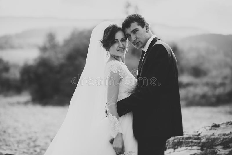 Handsome romantic groom and beautiful bride posing near river in scenic mountains.  royalty free stock photos