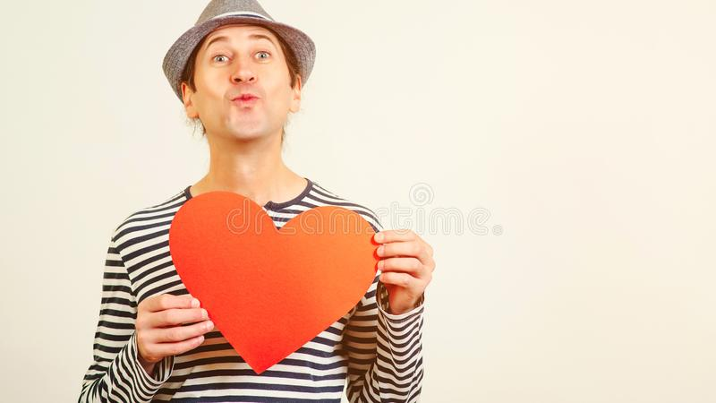 Handsome romantic guy is making airkiss. Happy Valentines Day. Funny man holding a red paper heart, on white background. Cope. Space. Guy holding heart postcard stock image