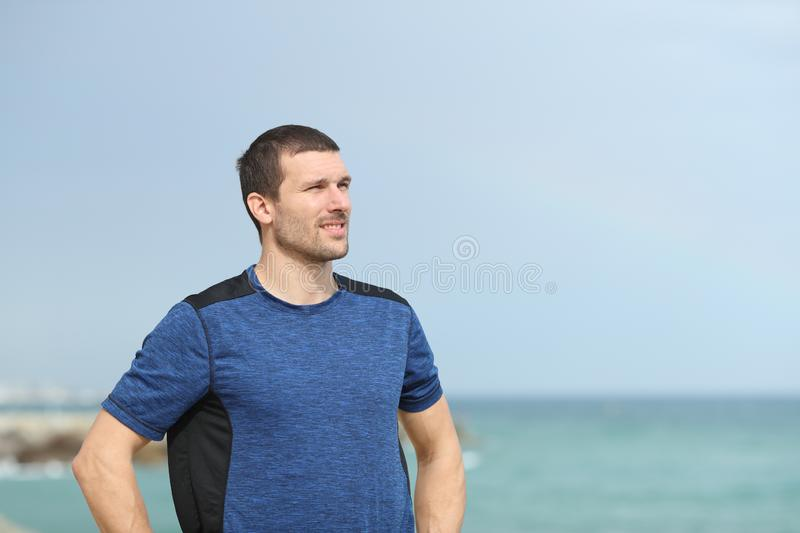 Runner looking away on the beach. Handsome runner looking away on the beach royalty free stock photos