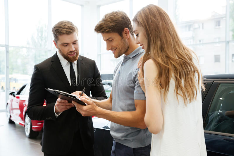 Handsome salesman filing documents with his happy clients. At the dealership stock images