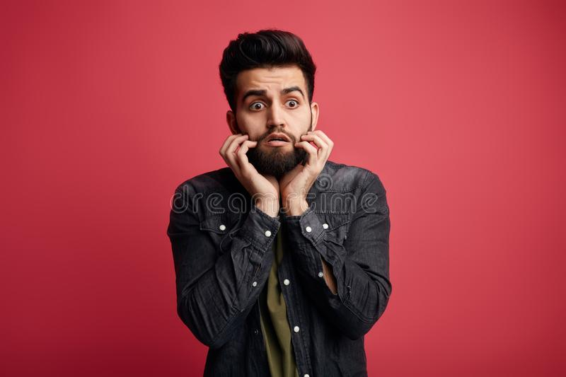 Handsome scared man with fingers on his mouth, being afraid of something, stock images