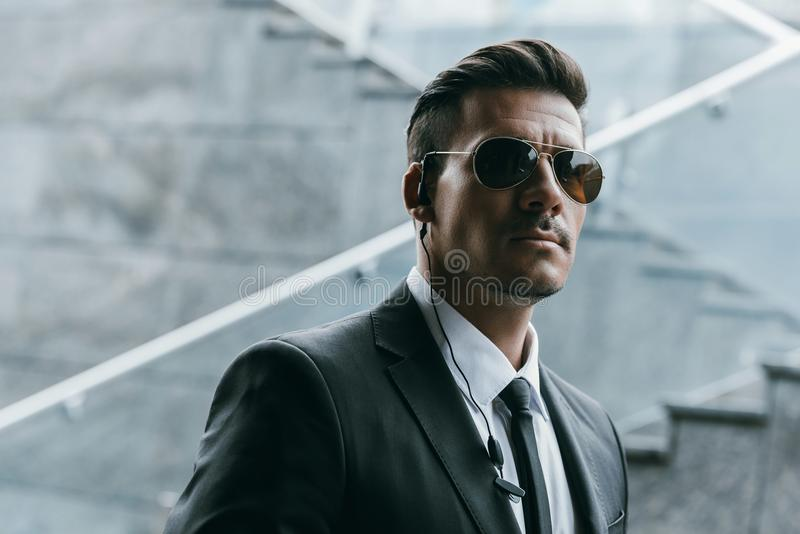 handsome security guard standing in sunglasses stock images