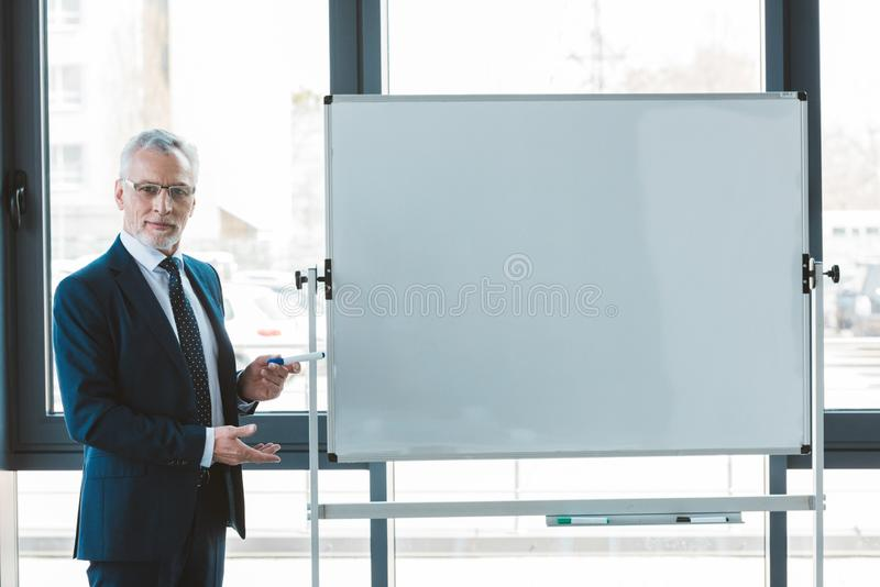 Handsome senior businessman in eyeglasses pointing at blank whiteboard and looking. At camera stock photo