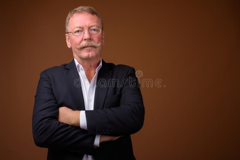 Handsome senior businessman with mustache wearing suit and looking at camera. Studio shot of handsome senior businessman with mustache wearing eyeglasses against stock photo