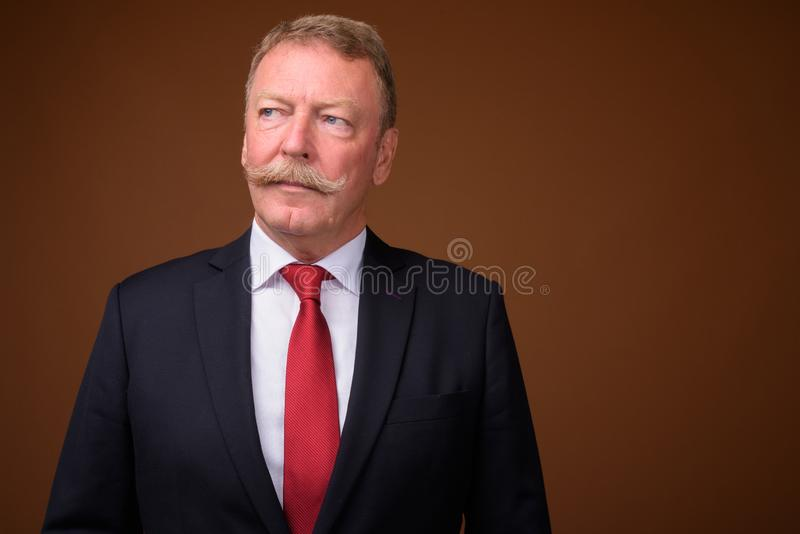 Handsome senior businessman wearing suit and tie while thinking. Studio shot of handsome senior businessman with mustache against brown background royalty free stock photos