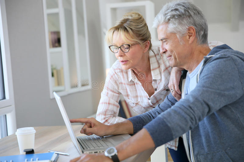 Handsome senior couple at home using laptop. Senior couple at home checking expenses on internet stock images