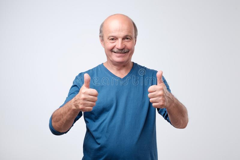 Handsome senior man in blue shirt shows thumb up. stock image