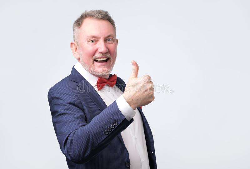 Handsome senior man in blue suit shows thumb up royalty free stock images