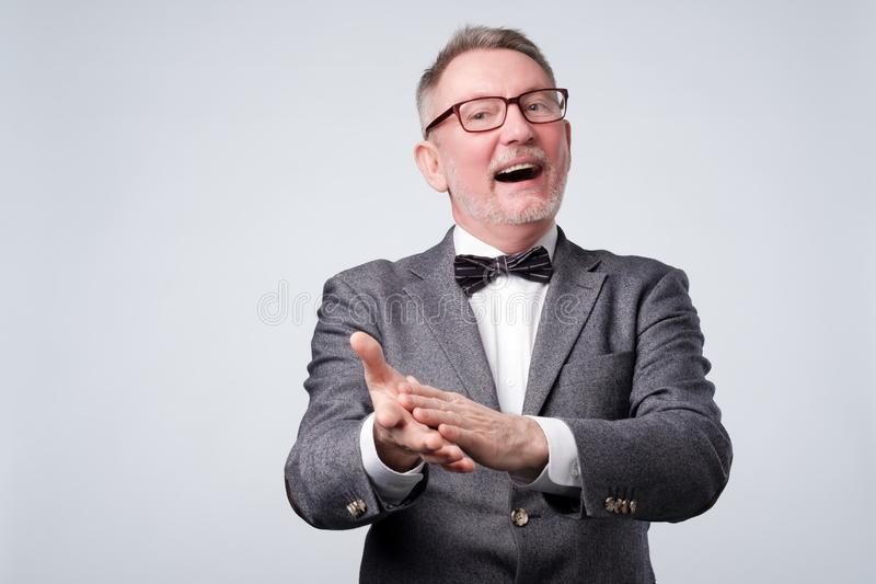 Handsome senior man in glasses and suit applauding stock photo