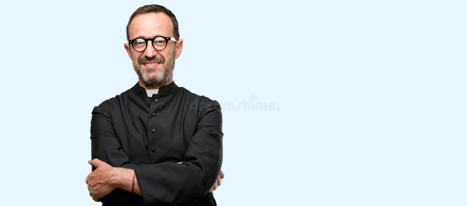 Handsome senior man isolated over blue background. Priest religion man with crossed arms confident and happy with a big natural smile laughing isolated over blue stock image