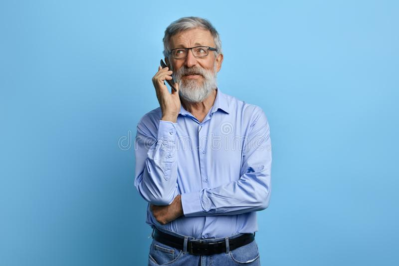 Handsome senior man looking up, talking on mobile phone royalty free stock photography