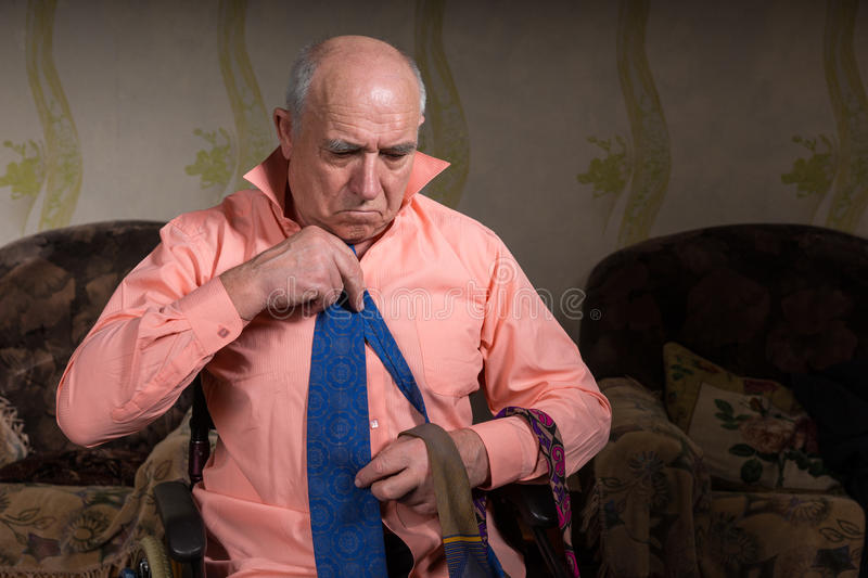 Handsome senior sad man is trying on a blue tie stock images