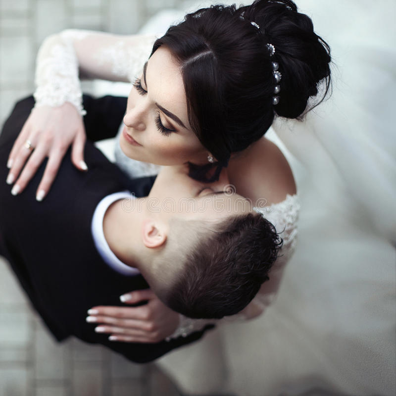 Handsome, sensual groom kissing beautiful bride on the neck closeup, view from above royalty free stock photos