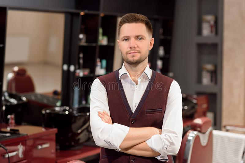Confident barber posing and looking at camera. royalty free stock image