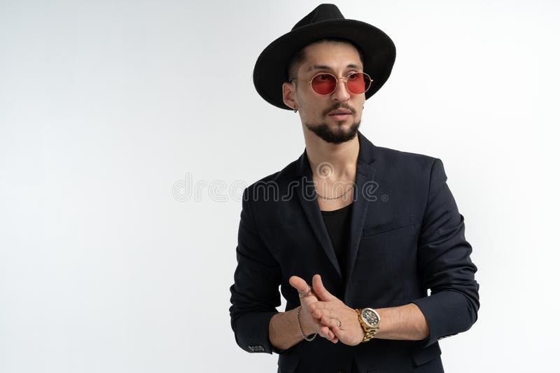 Handsome serious bearded man in black suit and hat, in red sunglasses posing isolated against white background, looking royalty free stock photos