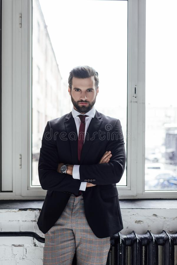 handsome serious businessman posing with crossed arms royalty free stock photography