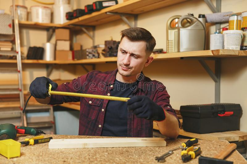 Handsome smiling young man working in carpentry workshop at wooden table place with piece of wood. Handsome serious caucasian young man in plaid shirt, black T stock photo