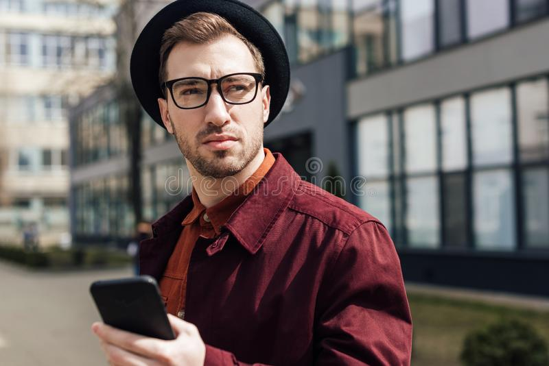 handsome serious man in eyeglasses and hat royalty free stock photography