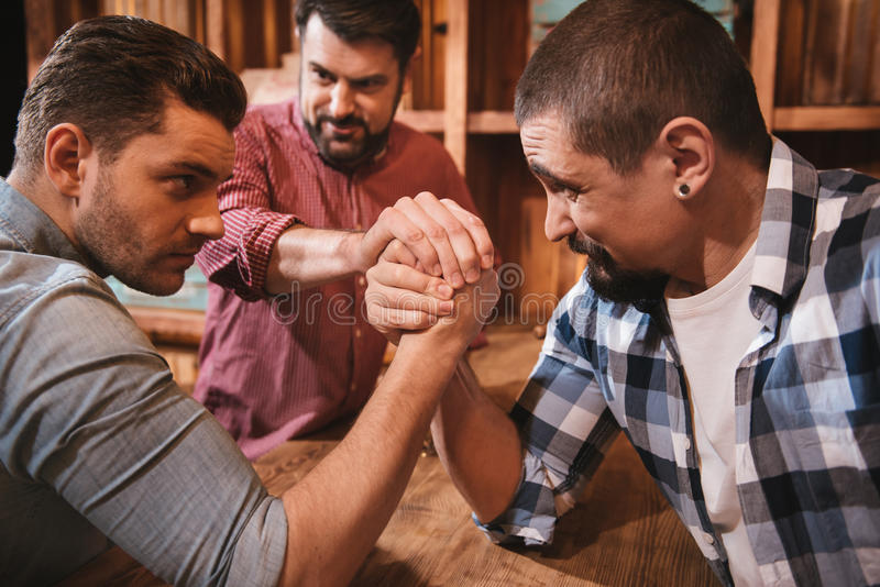 Handsome serious men preparing to start an armwrestling match. Fixed gaze. Handsome serious concentrated men looking at each other and gathering their strength stock photography