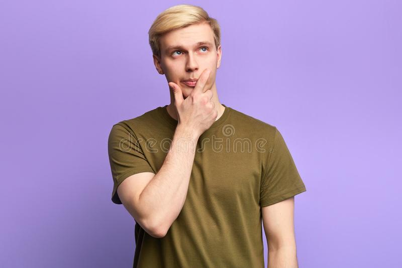 Handsome serious young man looking up with thoughtful look stock photo