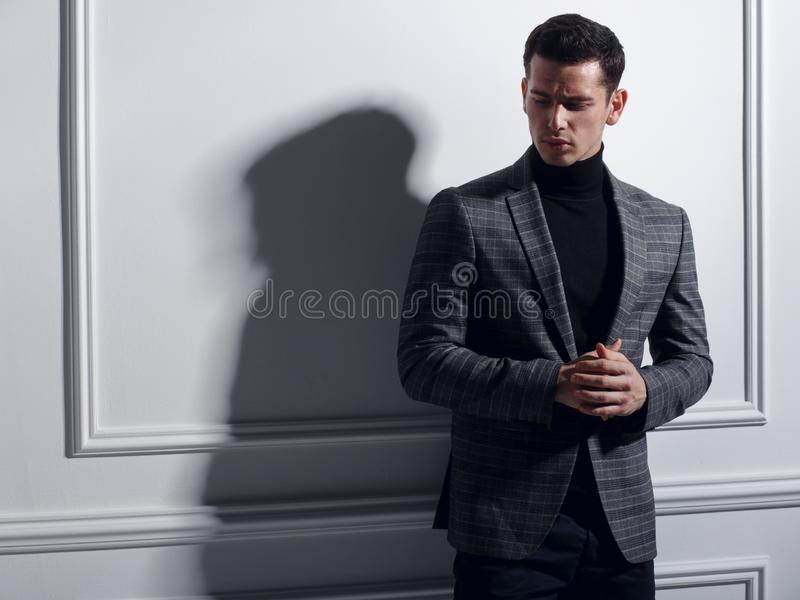 Handsome, serious young man posing in studio near white wall in elegantly gray suit, shadow. Business man concept. stock photo