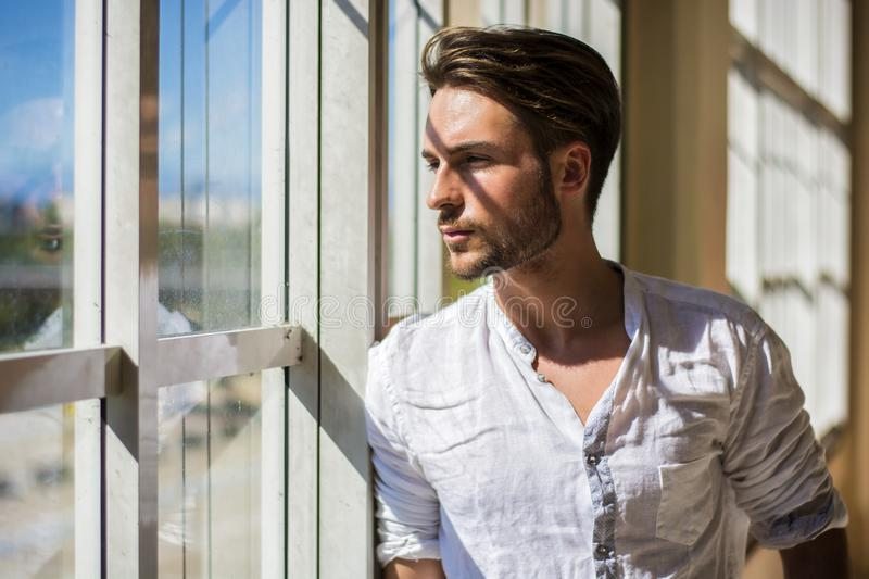 Serious young man standing inside modern building royalty free stock photos