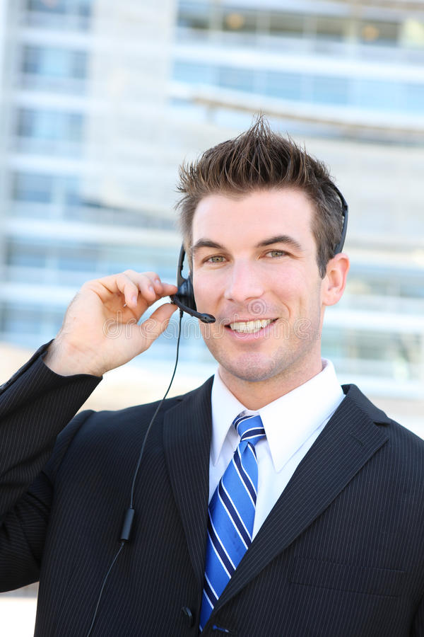 Handsome Service Man. A young handsome customer service man with headset outside company building stock photo