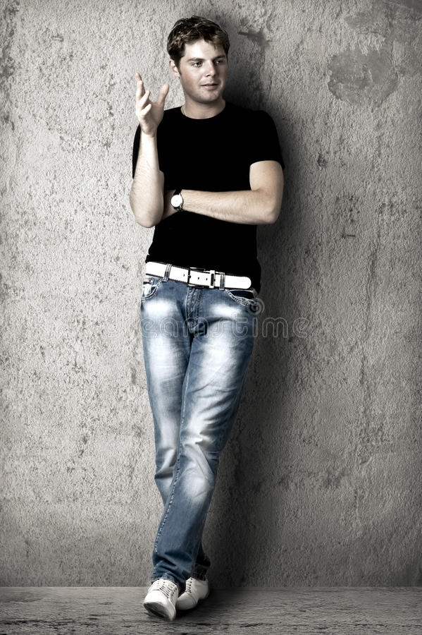 Handsome man in black t-shirt. Young handsome man in black t-shirt and blue jeans is leaning against the wall stock photography