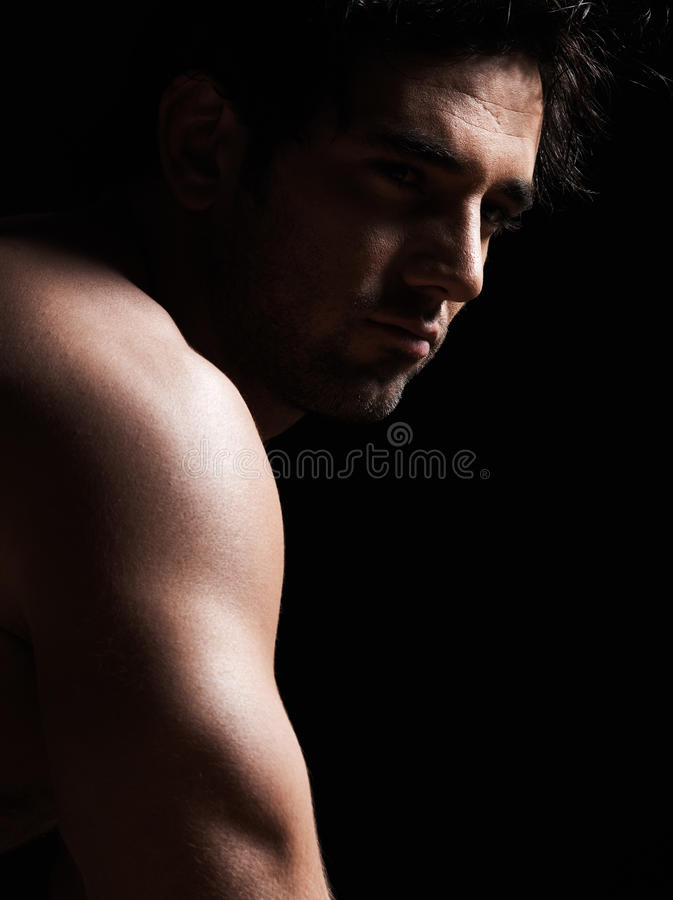 Handsome topless macho man portrait. Handsome caucasian topless macho man portrait topless muscular in studio black background royalty free stock images