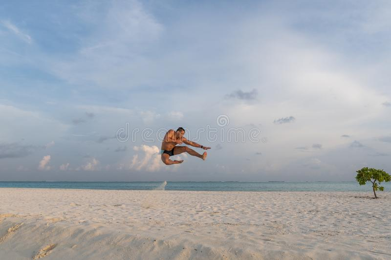 Handsome sexy topless male model jumping on the beach stock image